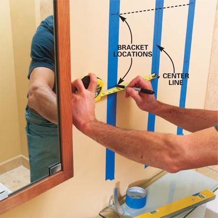 <b>Photo 4: Mark the shelf bracket locations</b></br> Apply a strip of 2-in. wide masking tape above the center of the toilet and on both sides where the shelf brackets will be mounted. Draw a center line with a level and mark the heights of the shelves on the center tape. Transfer the heights to the bracket tape with a 2-ft. level. Then measure from the center line to mark the exact left and right locations for the brackets.