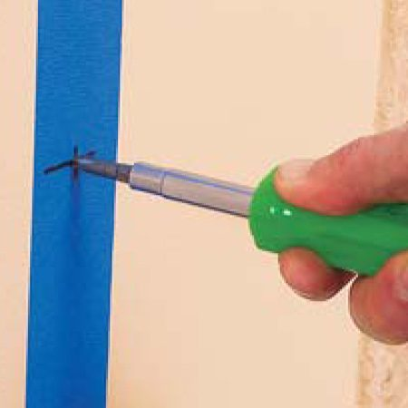 <b>Photo 5: Make indents at the marks</b></br> Indent the drywall at the marks with a Phillips head screwdriver and remove the tape.