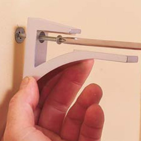 <b>Photo 7: Install the brackets. </b></br> Screw the brackets to the wall using the screws included with the anchors.