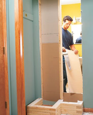 <b>Photo 12: Open up the wall. </b></br> Use the corner cuts from inside the bathroom to redraw the top and bottom cuts, adding 1/4 in. to the top and bottom for wiggle room. Cut out the bathroom drywall from the bathroom side. Remove the thin strip of drywall that covers the center stud (Photo 13).