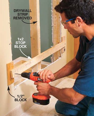 <b>Photo 13: Install stop blocks. </b><br/>Tack four 1/2-in. thick spacer blocks about 6 in. in from the top and bottom edges of the opening, then screw 1x2 stop blocks across both bays with 3-in. screws.
