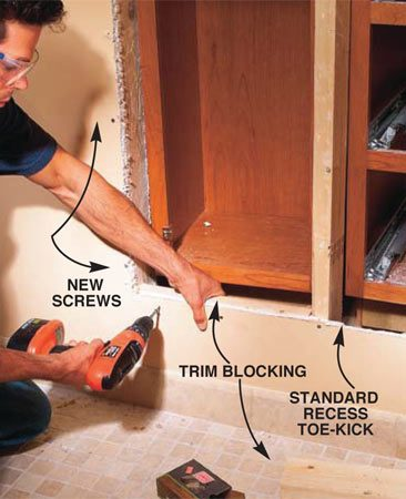 <b>Photo 15: Attach blocking to the drywall</b></br> Screw the bathroom-side drywall into the shifted studs. Push back the cabinets a few inches and screw 2x4 blocking to the drywall at the top and bottom for trim backing.