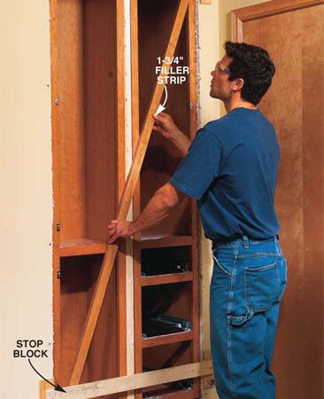 <b>Photo 16: Pull the cabinets flush against the stop blocks. </b></br> Rip the 3/4-in. filler strip to 1-3/4 in. wide and cut it the exact length of the cabinet face frames. Slip the filler into the opening, then place it between the cabinets. Pull the cabinets against the stop blocks.