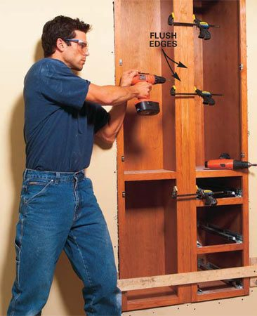 <b>Photo 17: Install the filler strip</b></br> Clamp the filler strip flush with the face of the cabinet frames and with the top and bottom. You may have to shim under the cabinet bases to get the tops and bottoms aligned. Then drill pilot, clearance and screwhead countersink holes and screw both cabinets to the filler strip with 2-1/2 in. screws spaced about every 12 in.