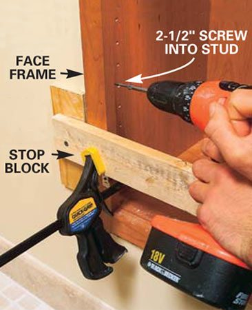 <b>Photo 18: Install the face frames</b><br/>Hold the face frames tight against the stop blocks with clamps and screw the cabinets to the studs with 2-1/2 in. screws spaced about every 12 in. Be careful not to overtighten the screws and pull them through the cabinet sides.