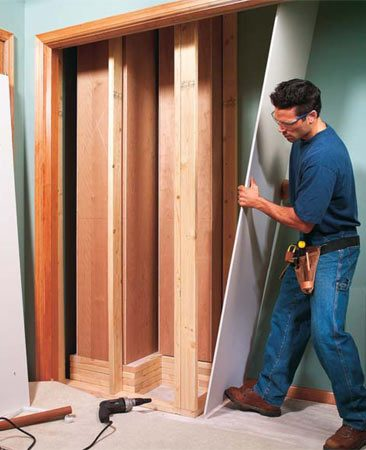 <b>Photo 20: Finish the cabinets</b></br> Frame 2x4 stud walls directly behind the cabinets. Nail the bottom plates into the subflooring and the top plates into the ceiling framing with 10d nails. Use construction adhesive to glue any plates and studs that join surfaces that don't have underlying framing. Hang and tape the drywall and corner bead, then paint.