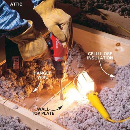 <b>Photo 2: Drill through top plate </b></br> Push aside the insulation to locate the coat hanger wire and the wall top plates. Drill a 3/4-in. hole through the center of the top plates at the heater and thermostat locations.