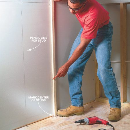 <b>Photo 2: Show stud locations</b></br> Mark the center of wall framing members on the floor with a pencil or marker. When you secure the upper sheets of drywall, make sure to center a fastener on each framing member before hanging the lower sheet. Then align a straightedge with the fastener and the marks on the floor and draw a pencil line to mark the center of the framing.