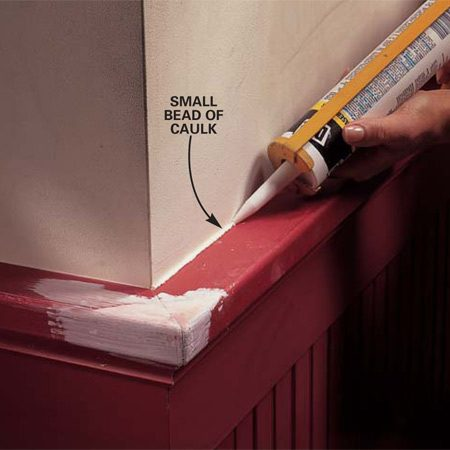 <b>Photo 6: Caulk cracks and gaps</b></br> Apply a small bead of paintable caulk to the crack between the wood and the wall.