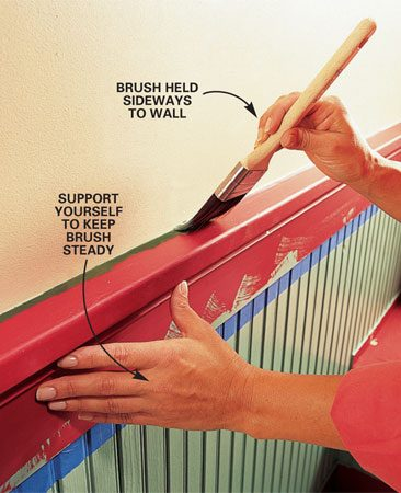 <b>Photo 13: Cut in along the wall</b></br> Load the 1-1/2 in. brush with paint and drag one side over the edge of the pail. Holding the dry side of the brush toward the wall, carefully set the tip of the brush close to the wall line. Apply a little pressure and pull the brush along the line. Guide the paint up to the line by manipulating the pressure and position of the brush's tip as you pull it along.