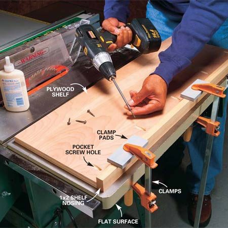 <b>Photo 7: Shelf nosing technique</b></br> Drill pockets along the edge of the plywood shelf. Clamp shelf nosing to a perfectly flat surface like the table saw top shown here. Spread a thin layer of glue along the edge of the plywood and screw the plywood to the shelf nosing. The pocket screws will draw the plywood down, resulting in a flush joint when you flip the shelf over.