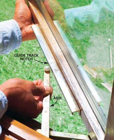 <b>Photo 2: Release the window</b></br> Open the window until the crank arm guide bushing aligns with the notch in the guide track (use a locking pliers for a crank handle and push out on the window to help it open). Press down on the arm to free the bushing from the track, and then push out the window until the bushing clears the track.
