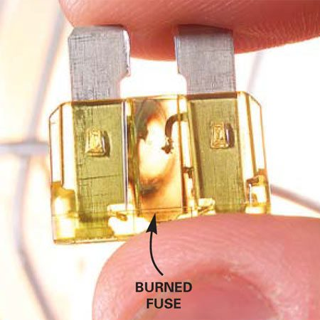 <b>Photo 6: Burned fuse</b></br> Hold the fuse up to the light to see if it's burned out. You'll see a fine wire connecting the two sides if the fuse is good. If a section of that wire has burned away, the fuse is bad.
