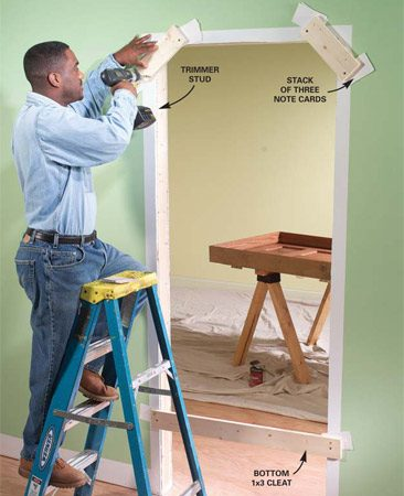 <b>Photo 3: Nail on stops</b></br> Nail temporary cleats to the wall opposite the door opening to act as stops for the door frame. To ensure the jambs are centered in the wall, shim them away from the drywall slightly with a stack of three note cards as shown.