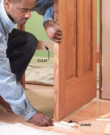 <b>Photo 4: Set the door in the opening</b></br> Push the door and frame into the opening. Open the door and shim the bottom edge of the open door to keep the frame tight against the stops on the other side.