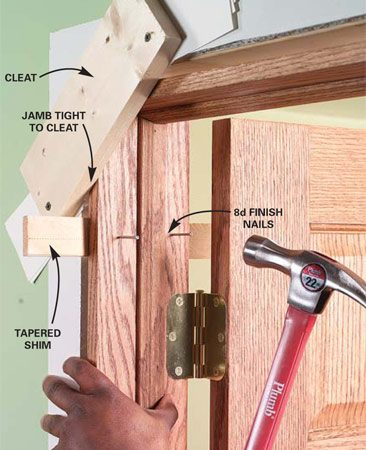 <b>Photo 10: Shim and nail the top corner</b></br> Center the frame in the opening. Slip a shim in from each side of the jamb (make sure the frame is pushed against the cleats) and nail the top sides of the door frame into the trimmer studs. The jamb should be perpendicular to your temporary cleats. Be careful not to twist the jamb as you nail it.