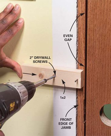 <b>Photo 7: Lock the strike-side jamb in place</b></br> Tack a 4-in. 1x2 to the front edge of the jamb with a 4d finish nail. Set up an even 3/16-in. gap between the door and the strike-side jamb. Then screw the block to the studs to hold the jamb in this position.