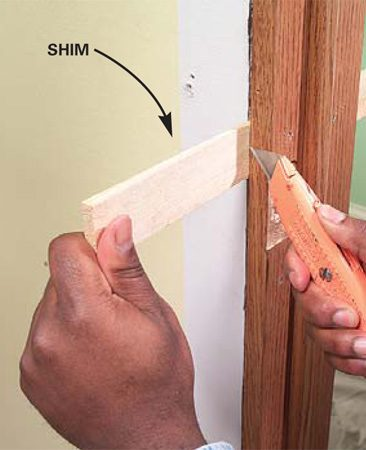 <b>Photo 9:  Break away the shims</b></br> Score the shims several times with a sharp blade and then snap them off to make way for the trim.