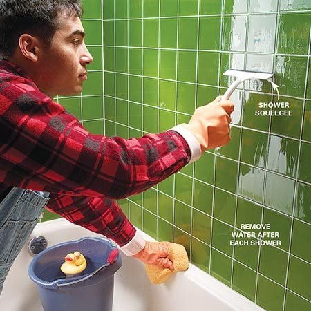 <b>Squeegee the tile clean</b></br> Rinse the entire tiled surface thoroughly with a dripping wet sponge. Push it back and forth across the top of the wall so rinse water streams to the bottom of the wall. Repeat until all cleaner is removed. Then, start at the top of the tile with a bathroom squeegee and move downward to remove as much water as possible.