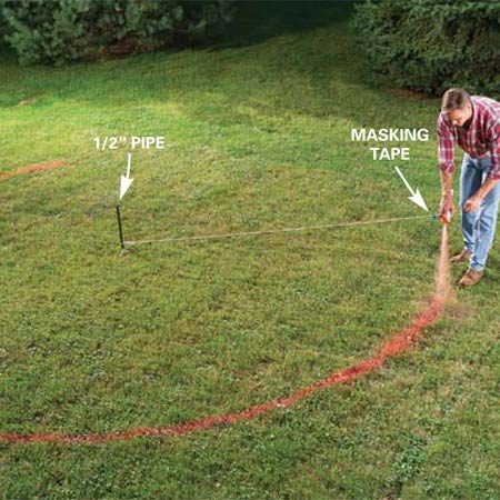 <b>Photo 1:  Mark the fire ring and patio</b></br> Drive a pipe firmly into the ground at the center of the fire ring. Loop a string over the stake and measure out 9 ft. Mark this point with tape. Hold a can of marking spray paint at the tape and spray the complete circle.