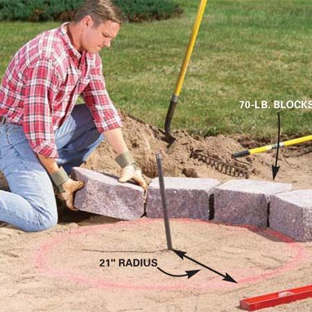 <b>Photo 5: Place the first row of stones</b></br> Draw a 21-in. radius circle with the string and marking paint. Lay the first row of retaining wall stones (12 in our case) along the line, minimizing the gaps between them. Twist each stone back and forth a few times in the sand to firmly set it. Make the tops level.