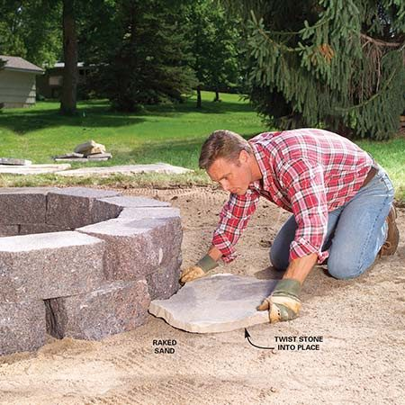 <b>Photo 7: Fit the flagstones to the fire ring</b></br> Spread 1 in. of sand over the sitting area. Fit the first flagstone tightly to the fire ring. Twist it into the sand to firmly set it. If it rocks, add or remove sand to stabilize it.