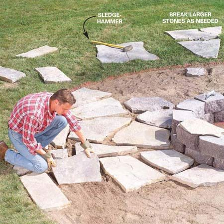 <b>Photo 8: Finish laying the stone</b></br> Fit and set stones out to the circle's edge. Keep the flagstone edges flush to one another and leave 2- to 4-in. spaces in between. You can break larger flagstones with a sledgehammer. <strong>Caution:</strong> Wear eye protection when breaking stone.