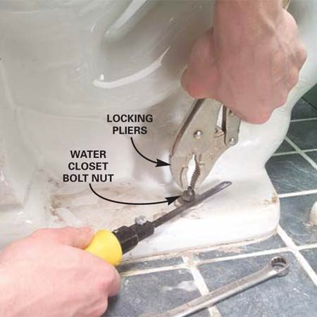 <b>Photo 1: Loosen the bolts</b></br> Unscrew the water closet nut with a wrench. If the bolt spins along with the nut, grab the exposed bolt above the nut with locking pliers. Loosen the nut just enough to squeeze in a hacksaw blade below the nut and saw through the bolt. <strong>TIP:</strong> Use a close-quarters hacksaw like the one shown or wrap a rag around a bare blade.