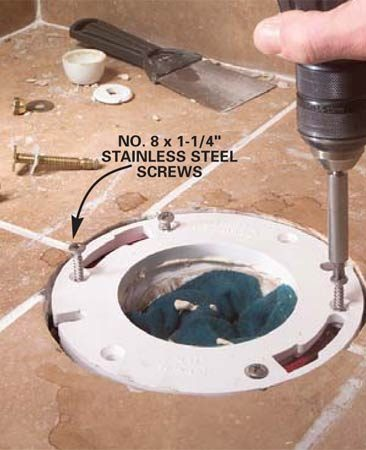 <b>Photo 8: Screw in the extender ring</b></br> Line up the holes of the extender ring with the flange holes and screw both parts into the floor with No. 8 x 1-1/4 in. stainless steel screws. Wipe away excess caulk and reset the toilet (Photos 11 – 14).