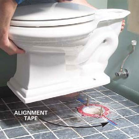 <b>Photo 12: Reset the toilet</b></br> Align the bolt holes with the masking tape and lower the toilet bowl straight over the bolts. Push down on the rim of the toilet to seat the wax ring, then close the lid and sit on the toilet for a few minutes to force the toilet all the way to the floor. Stop when the porcelain surface rests on the finished floor.
