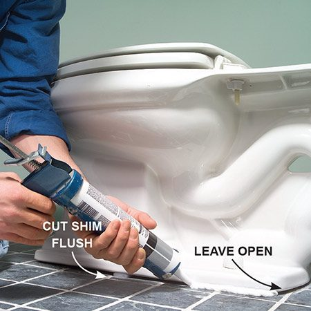 <b>Photo 14: Apply caulk</b></br> Caulk around the toilet base with silicone caulk, leaving the back end of the base uncaulked. The gap leaves a space for moisture under the toilet to escape. (Some local codes require caulk around the entire base.)