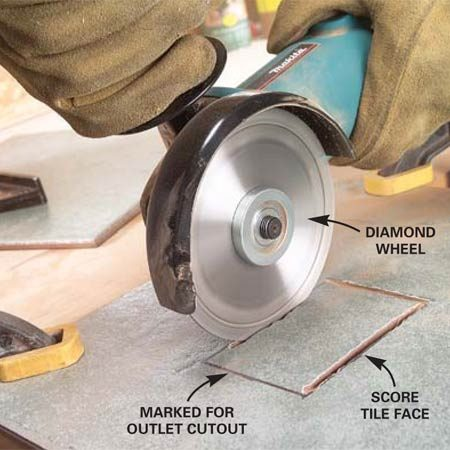 <b>Photo 5: Score the tile face</b></br> Mark the outline of the cut accurately on both the front and the back of the tile. Clamp the tile to your workbench and score the outline about 1/8 in. deep on the front with the diamond blade.