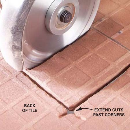 <b>Photo 6: Finish the cut on the back</b></br> Flip the tile over and cut through the tile from the back. Extend the cuts slightly past the lines at the corners to make crisp, square corners.