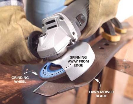 <b>Photo 7: Sharpen blades</b></br> Clamp the blade in a vise or to your workbench with hand clamps. Orient the grinder and adjust the blade guard to deflect sparks from your face and body. Align the grinding wheel with the angle on the blade. Start the grinder and move the grinding wheel steadily across the blade while applying light pressure.
