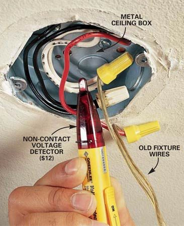 <b>Photo 2: Make sure the power is off</b></br> Test the wires to make sure the power is off. Move the tip of a non-contact voltage detector near each wire to make sure the power to all wires in the box is turned off (make sure the light switch is turned on). If the tester lights, switch off circuit breakers or loosen fuses one at a time until the tester light goes off. Disconnect the wires from the light fixture. Leave other wires connected and tucked into the electrical box.