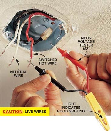 <b>Photo 4: Test for ground</b></br> Touch the leads of a neon voltage tester between the hot wire and the metal box (or between the hot wire and bare copper ground wire if you have one). If the tester lights, the metal box or bare copper wire is grounded and you can proceed. If the tester doesn't light, indicating there is no ground, call in a licensed electrician to supply one. (It's often difficult.) Turn off the power at the main circuit panel before continuing.