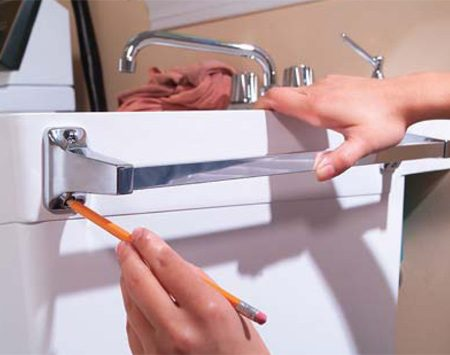 <b>Photo 1: Mark the holes</b></br> Mark the location of your towel bar on the thick rim near the top of the sink. You may need to shorten the bar first by pulling the bar from the ends and trimming it to about 16 in.