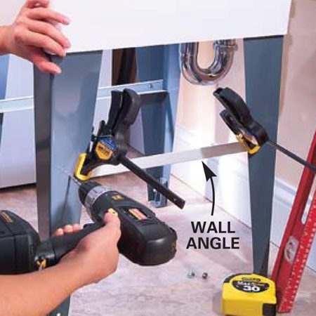 <b>Photo 2: Attach the angles</b></br> Clamp pieces of ceiling angle or aluminum angle to your sink legs (about 11 in. from the floor) and drill through with a 3/16-in. bit. Insert 1/2-in. long No. 8-24 bolts from the inside and thread on acorn nuts to cover sharp bolt edges.
