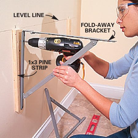 <b>Photo 3: Screw the brackets to the wall</b></br> Draw a level line 1-1/2 in. below the finished height of your laundry table. We made ours 33 in. high including the thickness of the top. Screw 1x3 pine strips to the wall into the studs behind. If you have a concrete wall, predrill holes for anchors and then screw the steel laundry table brackets to the strips and wall with 2-1/2 in. screws.