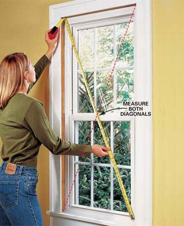 <b>Photot 5: Check for square</b><br/>Close and lock the sash. Measure diagonally across the new window. Slide shims behind the screw holes in the four corners and adjust them until the diagonal measurements from opposite corners are equal. Drive screws through the upper left and lower right screw holes.