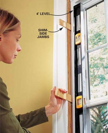 <b>Photo 6: Plumb the window</b><br/>Hold a level against the side jamb and slide wood shims behind each remaining screw hole until the side jamb of the window is straight. Snug up all of the screws and check to make sure the sashes slide easily and align perfectly where they meet in the middle. Be careful; overtightening the screws could warp the vinyl jamb. Cut off the shims with a sharp utility knife.