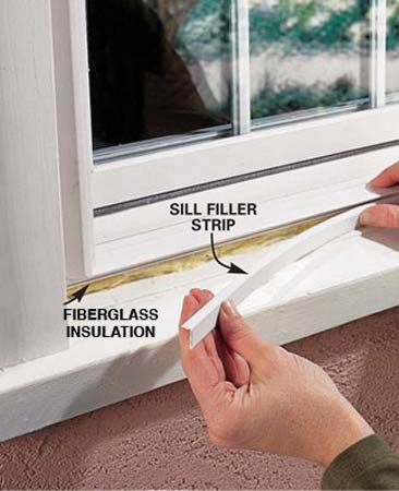 <b>Photo 8: Insulate</b><br/>Stuff fiberglass insulation in the gap under the sill of the new vinyl window. Measure the size of the gap and cut the vinyl filler strip to fit. Use a sharp utility knife and straightedge or tin snips to cut the vinyl. Press the filler into place.