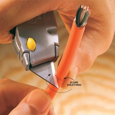 <b>Photo 1: Score the jacket</b></br> Score a circle around the cable jacket, but don't cut all the way through the plastic. This technique may look dangerous, but it's safe as long as you apply very light pressure with the knife and keep your thumb on the opposite side of the cord. Carefully guide the knife around the cable until you reach your starting point.