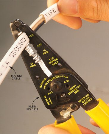 <b>Photo 1: Strip sheathing</b></br> Align the plastic-sheathed cable with the notch that matches the wire gauge you're using—either 14/2 or 12/2—and squeeze down to cut the sheathing. Slide the sheathing off to expose the wires underneath.