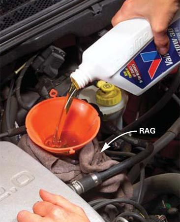 <b>Photo 1: Add the new oil</b></br> Add the oil amount specified in the owner's manual.