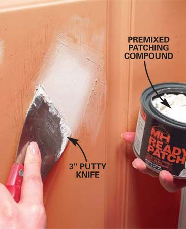 <b>Photo 2: Fill the dent</b></br> Press patching compound into the dent with a small putty knife, then smooth and feather out the edges as if you're spreading drywall mud.