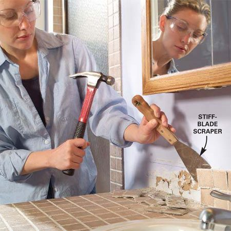 <b>Photo 3: Remove the backsplash</b></br> Chisel away the tile backsplash before removing the vanity top. If you have a plastic laminate backsplash, just cut the caulk seam with a utility knife where the backsplash meets the wall.