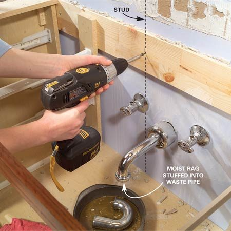 <b>Photo 6: Remove the vanity</b></br> Unscrew the vanity from the wall. If you don't see screws, look for large nails and use a pry bar to remove them. While you're at it, mark the wall stud locations. They'll come in handy later.