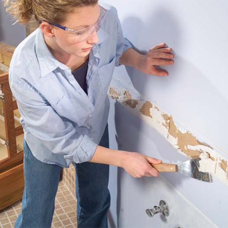<b>Photo 7: Clean up the wall</b></br> Scrape away any glue or caulk left on the wall with a sharp scraper. Be careful not to tear the drywall paper beyond the repair area. Remove any loose bits of paper.