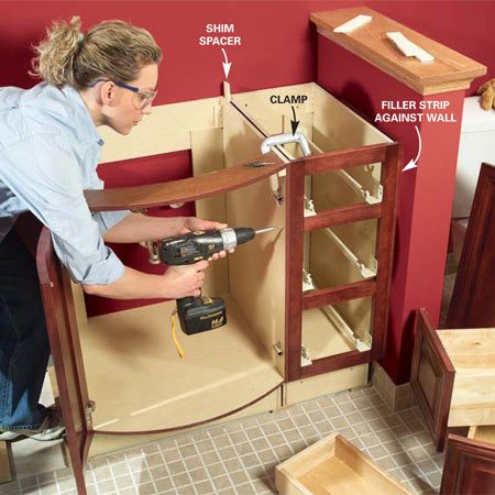 <b>Photo 12: Screw the frames together</b></br> Screw the cabinet frames together before screwing them to the walls. Flush the fronts, clamp them, drill a clearance and pilot hole, then drive a screw near the top, middle and bottom of the cabinets. Evenly space the cabinet sides and shim them near the back and screw them together near the back edge. Cut protruding shims flush after you screw the cabinets to the wall.
